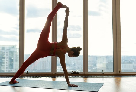 Confident female athlete is doing splits. She is standing on one leg and arm while raising another part up. Girl is stretching hand to her foot