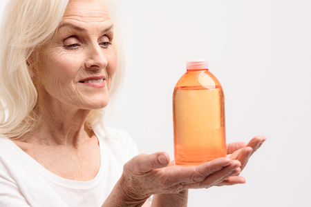 Happy smiling old lady keeping cosmetic