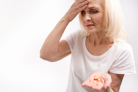Frowning old woman keeping medications