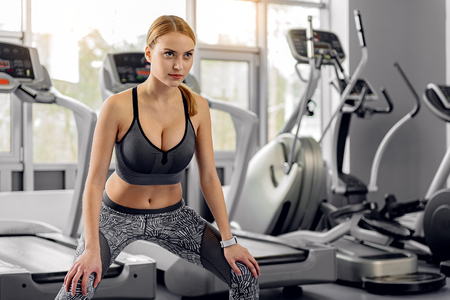 Careful woman limbering up in gym Stock Photo