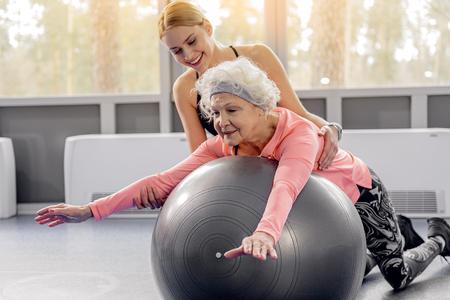 フィット ボールに寄りかかって笑顔の退職者 写真素材