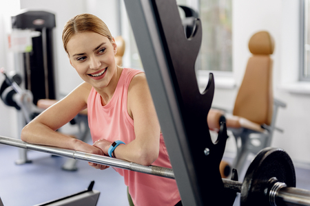 Cheerful girl reclining on equipment in gym Imagens
