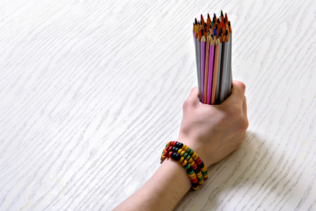 Girl griping various colored pencils Stock Photo