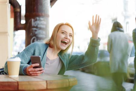 Happy blond girl waving hand to friend on street Stock Photo