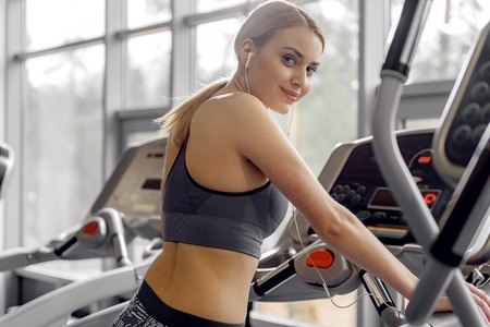 Cheerful female running in fitness center