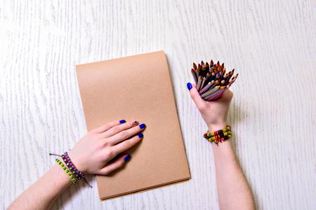 Woman keeping crayons and notebook