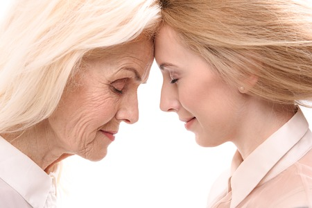 Old lady inclining forehead to younger woman Stock Photo