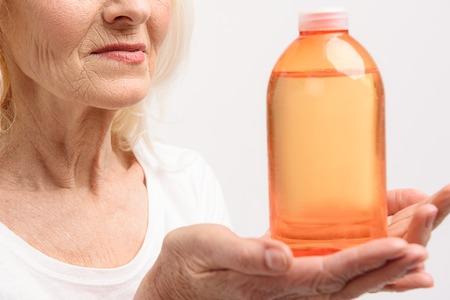 a jar stand: Smiling mature woman keeping orange bottle