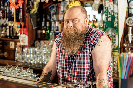 Thoughtful fat bartender situating at market stall