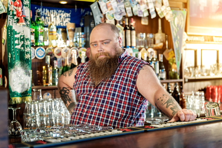 Calm fat male leaning on worktop in bar