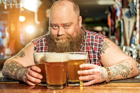 Cheerful bearded man placing glasses of beer
