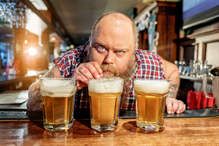 Fat male tasting alcohol beverage in dramshop Stock Photo