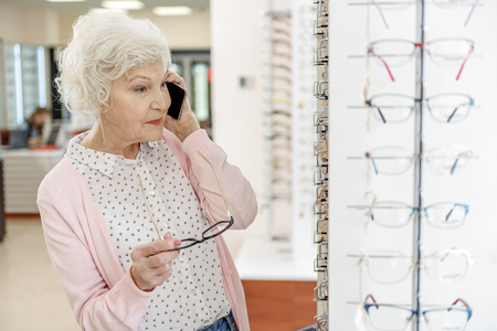 Stylish old woman in optic shop Stock Photo