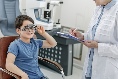 Happy glancing child in optic clinic Stock Photo