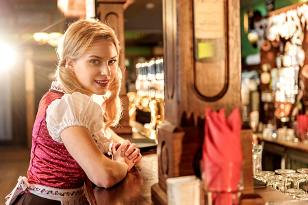 Cheerful young woman working at alehouse