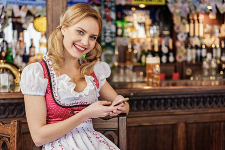 Cheerful female watching at cellphone in boozer