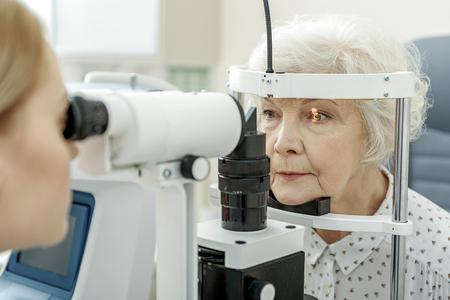 Młoda kobieta okulista przy użyciu aparatu
