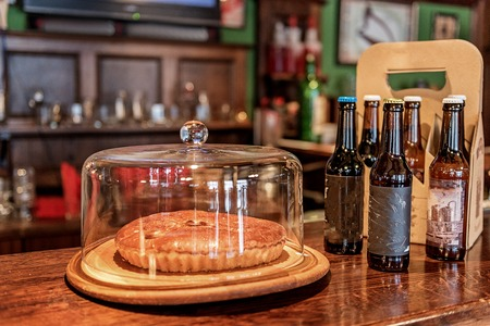 Pie and bottles of beer locating on bar