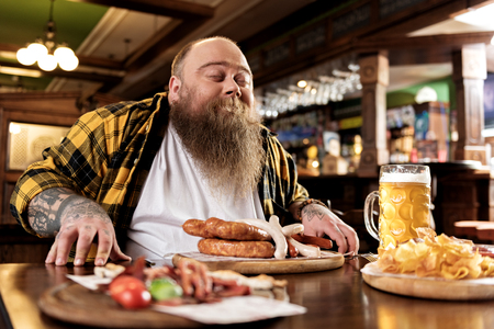 Glad fat male snuffing meal Stock Photo