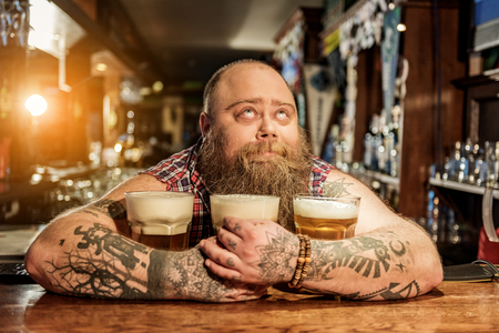 Pensive male embracing mugs of alcohol beverage