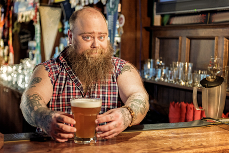 Outgoing fat man putting ale on table
