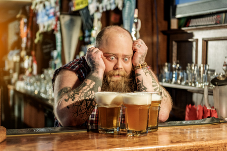 Wonder bearded male watching at beer Stock Photo