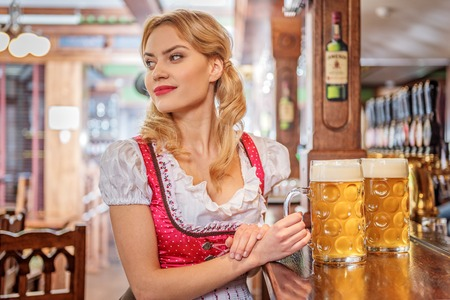 Pensive female drinking beer in pub