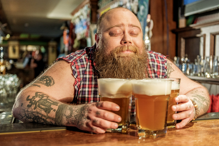 Glad fat man hugging alcohol in bar Stock Photo