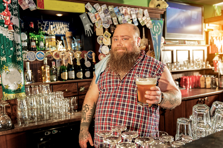 Happy bearded male tasting beverage in pub