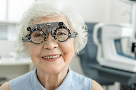 Hilarious smiling old female person checking eyesight