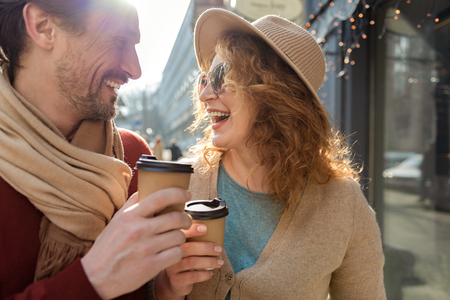 Carefree man and woman drinking beverages outdoors