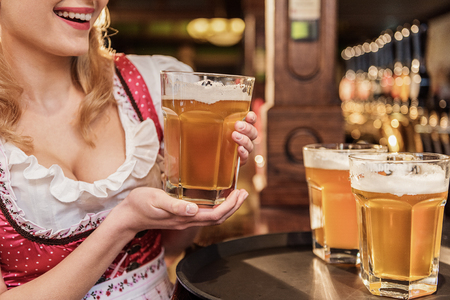 Outgoing woman arm keeping glass of beer