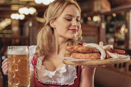 Happy female holding sausages and beer glass