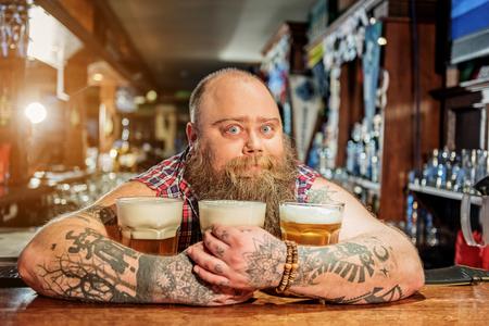 Surprised man hugging glasses of beer Stock Photo