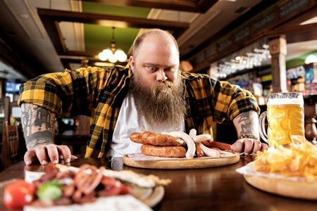Wonder bearded man eating food in boozer