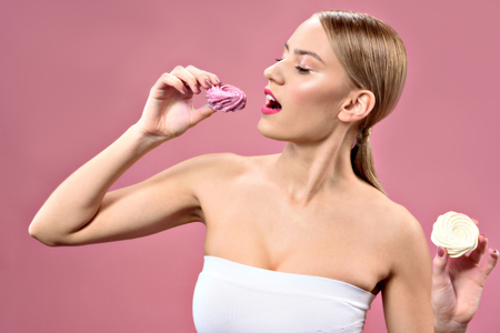 Young woman eating pink zephyr Stock Photo