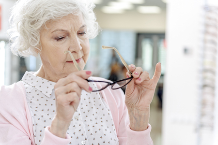 Interested old woman choosing eyewear