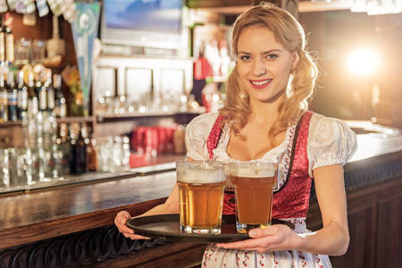 Cheerful woman holding tray with beer glasses Stock Photo