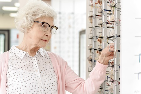 Concentrated mature woman in optic store