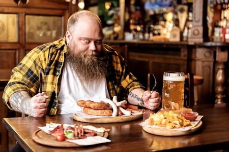 Wonder bearded male eating sausages in boozer