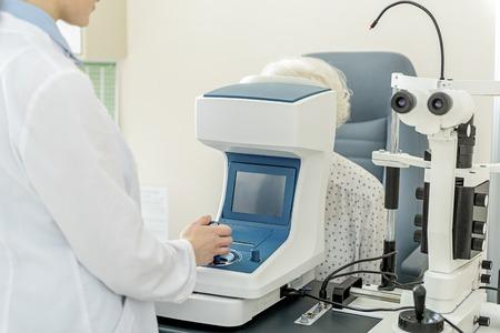 Jonge oogarts die werkt met speciale optische apparaten