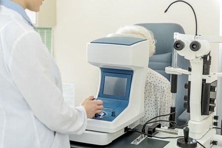 Young ophthalmologist working with special optical apparatus Stock Photo