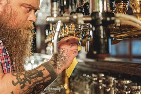 Calm bearded male washing beer tap Stock Photo