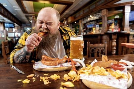 Glad bearded man swallowing sausages in tap-room