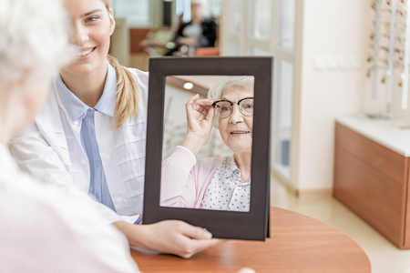 Store assistant keeping mirror for customer Stock Photo