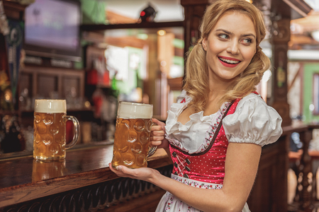 Outgoing woman serving glasses of beer Stock Photo