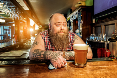 Pensive bearded man standing in tap-room Stock Photo