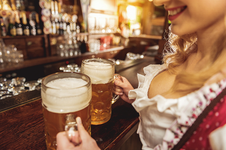 Hand of happy woman caring beer glasses Stock Photo