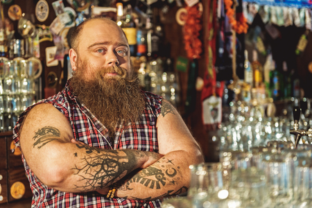 Cool bearded bartender situating in tap-room Stock Photo