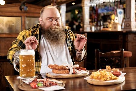 Pleasure bearded man eating food in boozer Stock Photo